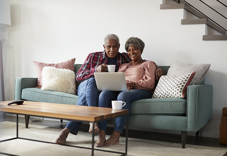 senior-couple-sofa-using-laptop